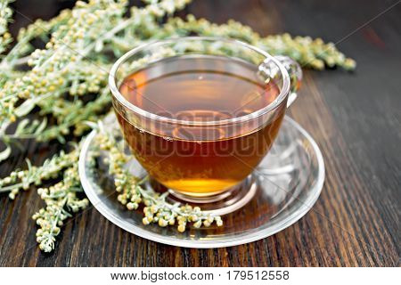 Tea With Gray Wormwood In Glass Cup On Table