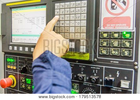 mechanical technician working with Control Panel of CNC machine center at tool workshop