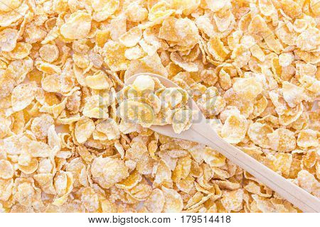 Cornflakes in a wooden spoon on cornflakes background. Close-up.