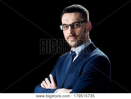 business, people and office concept - businessman in glasses over black background