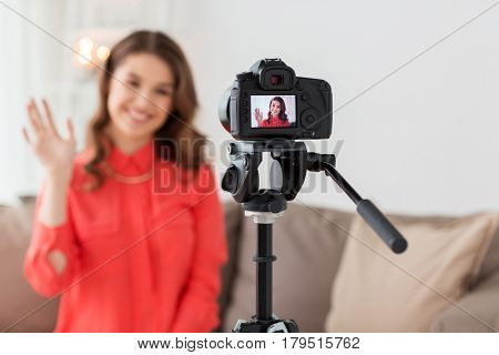 blogging, technology, videoblog, mass media and people concept - happy smiling young woman or blogger with camera recording video and waving hand at home