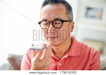 technology, people, lifestyle and communication concept - happy man using voice command recorder on smartphone at home
