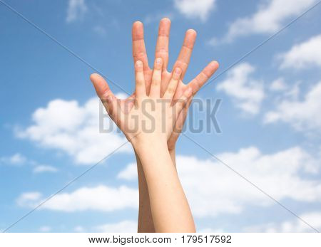 family, childhood, fatherhood and people concept - father and child holding hands together over blue sky and clouds background