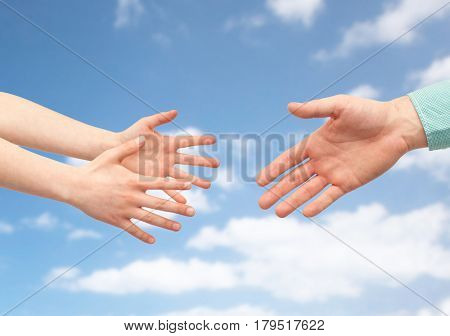 family, childhood, fatherhood, help and people concept - father and child hands over blue sky and clouds background