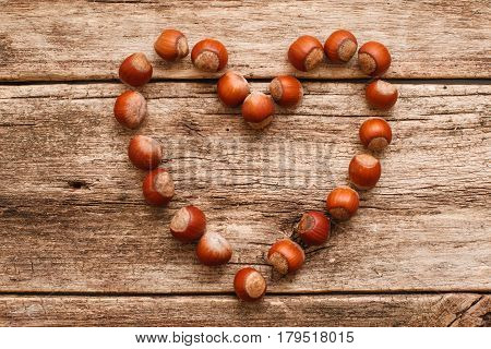 Heart made of hazelnuts on wood flat lay. Top view on wooden table with symbol of love made from filbert nuts. Autumn, harvest, feeling, fall, food ingredient concept