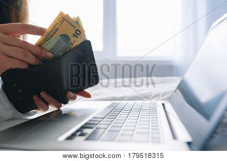 Internet business online, successful startup, freelance work. Unrecognizable woman put money into wallet over laptop, free space