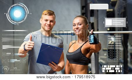 fitness, sport, exercising and diet concept - smiling young woman and personal trainer with clipboard showing thumbs up in gym over virtual charts