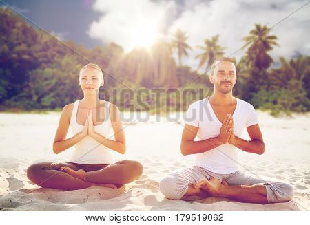 fitness, sport, people and healthy lifestyle concept - smiling couple making yoga in lotus posture meditating over exotic beach background