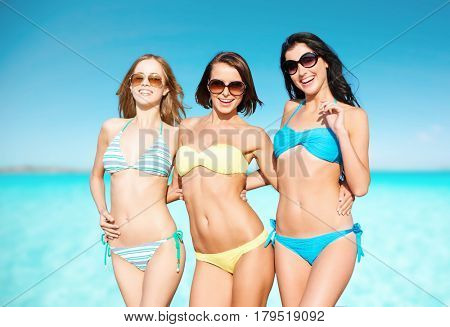 summer holidays, travel, people and vacation concept - happy young women in bikinis and shades over sea beach background