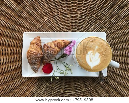 top view of hot cappuccino coffee drink with croissants decorate with flower on rattan wood table with copy space