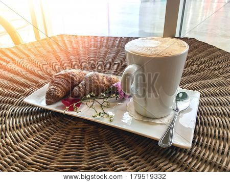 hot cappuccino coffee drink with croissants decorate with flower on rattan wood table