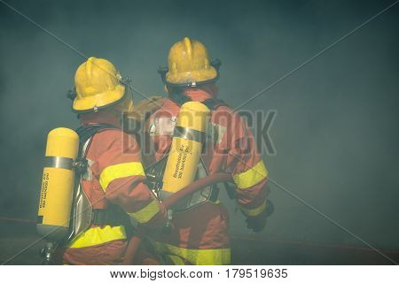 two firefighters fire fighting search and rescue surround with dark smoke in cinematic tone