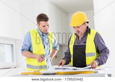 Architect and construction engineer indoor meeting. Building experts cooperation and project analysis. Real estate market.