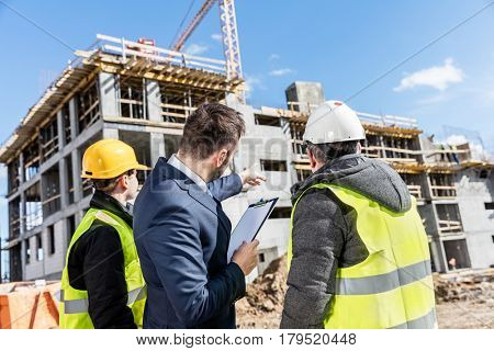 Engineers and investor meeting at the construction site. Supervisor pointing at a building and instructing the team. Real estate market.
