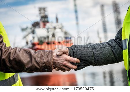 Shipbuilding deal concluded by a handshake of two engineers. Company contract