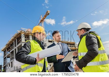 Engineer, worker and investor meeting at the construction site. Supervisor instructing the team. Real estate market.