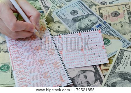 The hand is writting on lottery ticket on dollar background