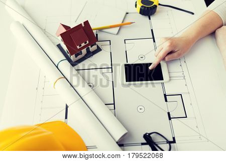 business, architecture, building, construction and people concept - close up of architect hand with living house blueprint and smarphone