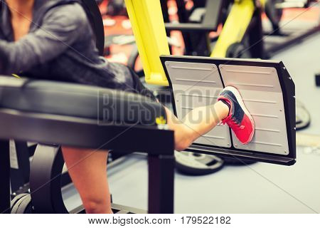 fitness, sport, bodybuilding, exercising and people concept - close up of young woman flexing muscles on leg press machine in gym