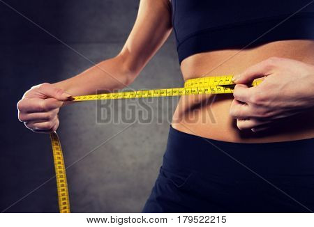 sport, fitness, weight loss, diet and people concept - close up of woman measuring waist size by tape in gym
