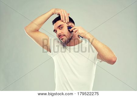 beauty, grooming and people concept - smiling young man shaving whisker with trimmer or electric shaver over gray background