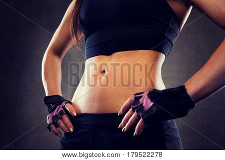 sport, fitness, bodybuilding, sportswear and people concept - close up of young woman body in gym