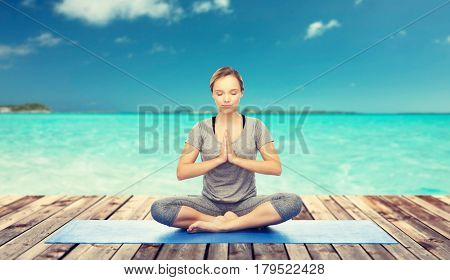 fitness, sport, people and healthy lifestyle concept - woman making yoga meditation in lotus pose on mat over sea and blue sky at resort background