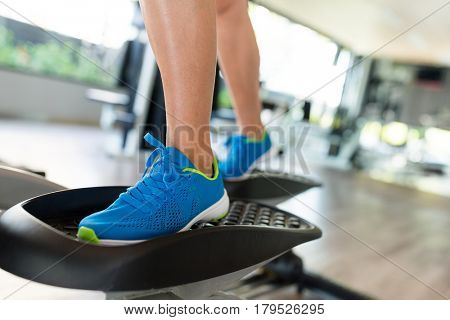 Woman working out on elliptical trainer in gym
