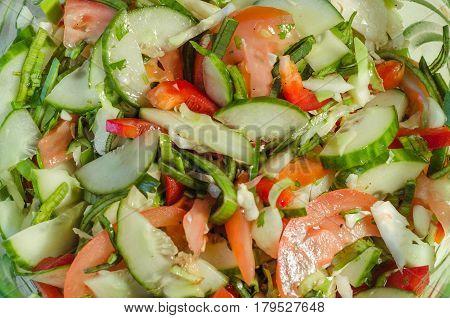 Vitamin finely cut salad of tomatoes, cucumbers, onions and greens closeup top view