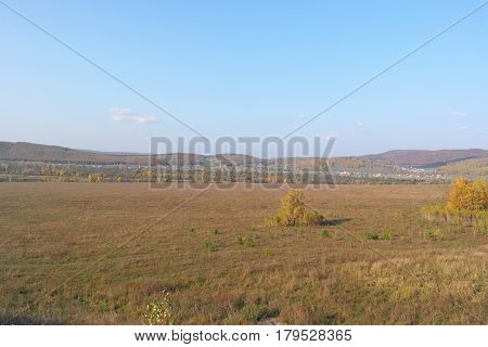 Beautiful autumn village landscape with field and sky