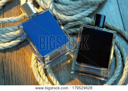 Two bottles of perfume for men and rope on woody table. Male beauty concept.