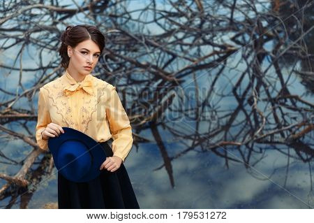outdoor fashion portrait of sensual stylish girl in vintage clothes with lake on the background. Young woman with romantic hairstyle and floppy hat. Female retro look