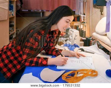 girl seamstress making notes at notebook. Fashion designer drawing sketches. Hobby sewing as a small business concept. Tailor measuring and writing down the results