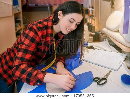 young seamstress making pattern on fabric with tailors chalk. Girl working with a sewing pattern. Hobby sewing as a small business concept. Tailor measuring textile material. Fashion designer works