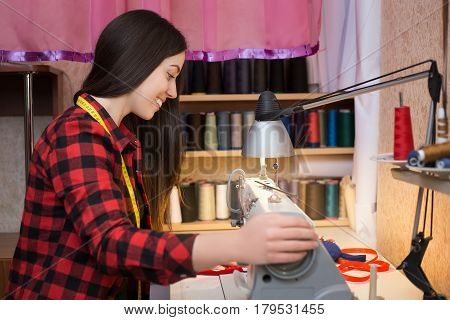 happy girl seamstress sitting and sews on sewing machine. Dressmaker work on the sewing machine. Tailor making a garment in her workplace