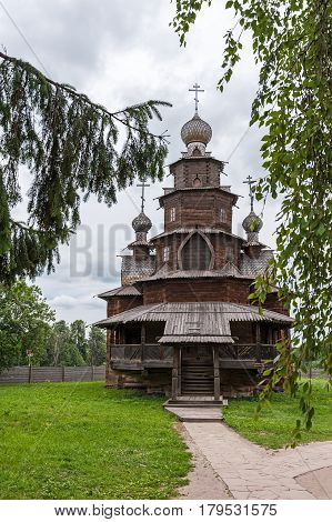 Suzdal is an old wooden Church from ebony in the summer among the trees on a cloudy cloudy day