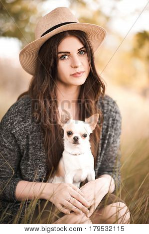 Beautiful girl 24-29 year old holding chihuahua puppy in park. Posing outdoors. Friendship. 20s.