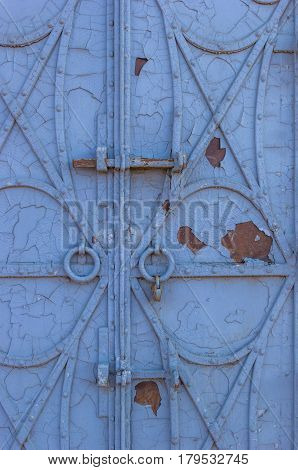 Old forged iron door with rivets and old peeling blue paint on it