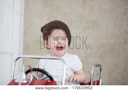 Child crying in red car. Kid in a brown hat