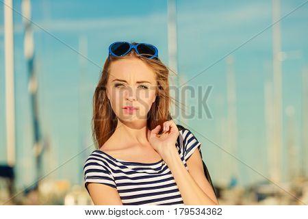 Summer fashion. Portrait girl in blue heart shaped sunglasses enjoying summer breeze at sunset in marina