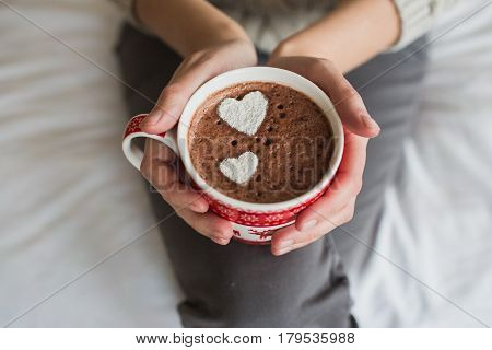 Woman hands holding a Cup of hot cocoa or hot chocolate for a background, traditional drink for the winter time, lifestyle photos, top view, Valentine's day