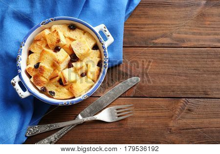 Bowl with delicious bread pudding and napkin on wooden table
