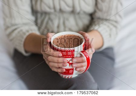 Woman hands holding a Cup of hot cocoa or hot chocolate for a background, traditional drink for the winter time, lifestyle photos, top view