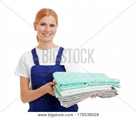 Beautiful woman with folded bed clothes on white background