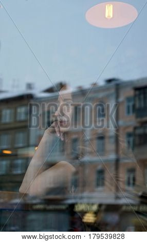 Profile of young girl, loneliness in coffee shop. She looks out the window, lost in thought. The window displays the old house and office building. City life, window reflection, urban style