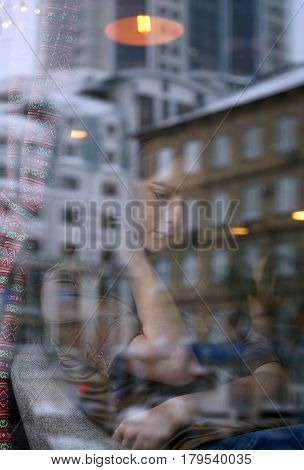Young girl waiting in cafe for someone, who late. Her hand near chin, head bowed. The window displays the old house and office building. City life, window reflection, urban style