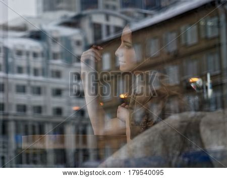 A sad young girl looks out the window and dreaming about something. She winds a lock of hair on her finger. On the glass reflection of house and office building. Concept: waiting, dream, loneliness