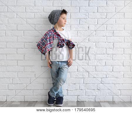 Cute stylish boy near light brick wall