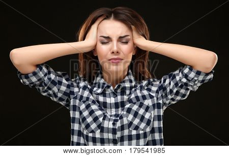 Beautiful young woman suffering from headache on black background