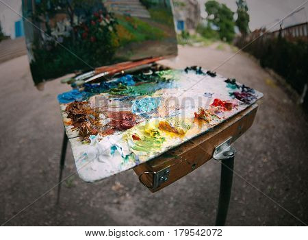 art palette with tubes of paint and brushes. acrylic paint on canvas palette. plein air.